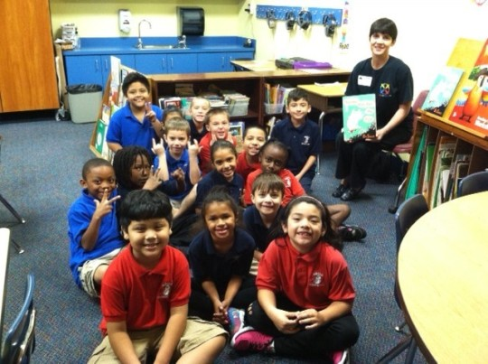 Alicia Long reading to a group of children in an elementary school